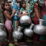 People wait in line with water pots as they collect water from a lorry from WASA in outskirts of Dhaka
